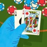 A hand wearing a blue surgical glove holding poker cards, depicting the suicide king in the suit of a COVID virus particle.