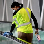 A worker cleans a walkway railing in the Boston Logan International Airport.