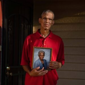 A man wearing a red shirt holding a photo of his mother.