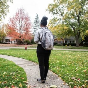 A girl wearing a backpack and a grey sweatshirt standing in a yard.