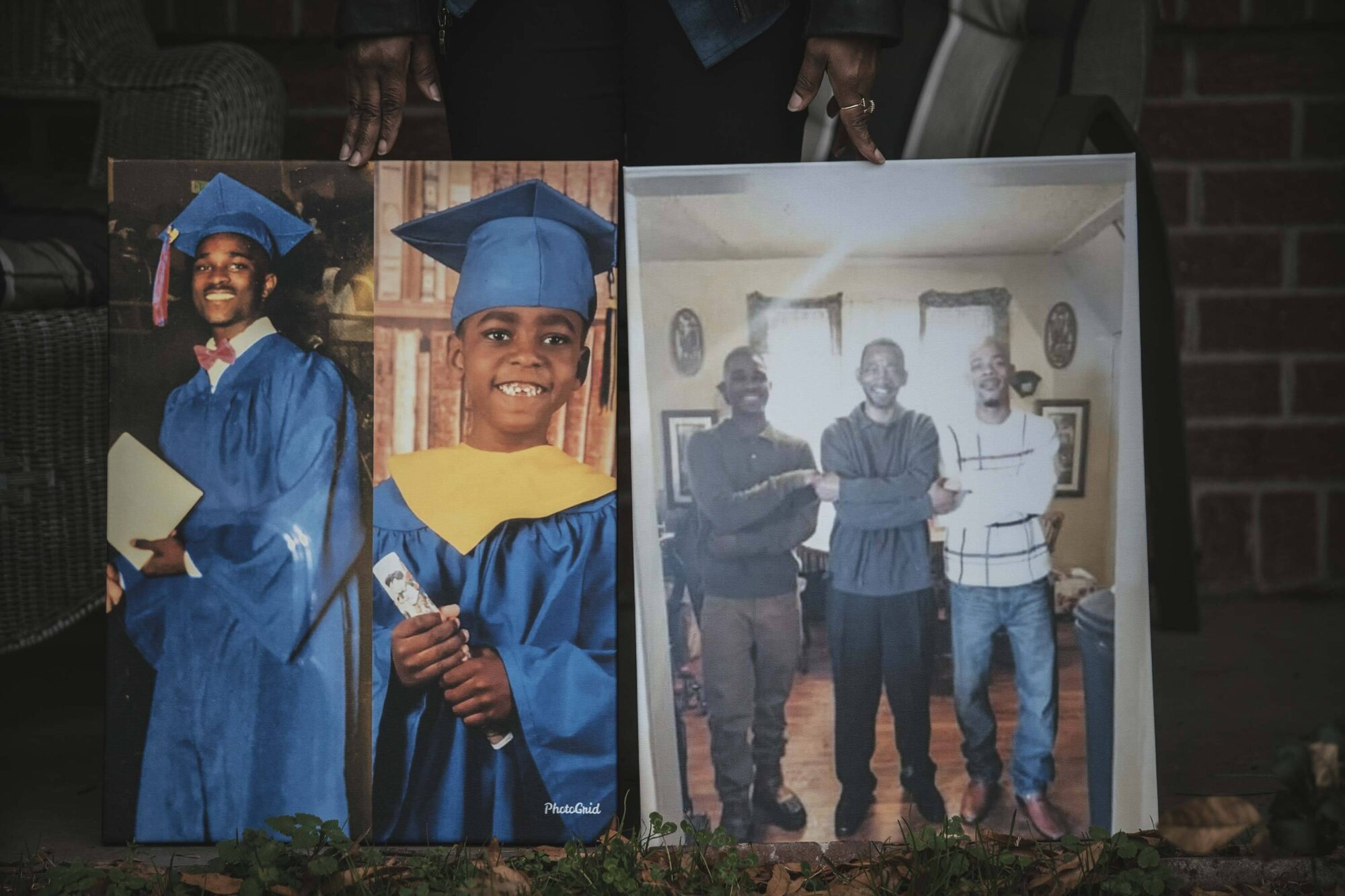 """Jeanette McClenton holds photographs of her son Duntate Young in a composite with his oldest son (left) and with his father, Leanell """"Troy"""" McClenton, and his cousin (right) while standing for a portrait outside her home in West Memphis, Arkansas."""