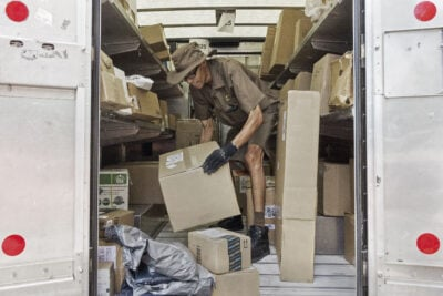 "A UPS worker sorts packages in the back of his truck. UPS, DHL and FedEx lobbied Congress to raise the ""de minimis threshold"" –– the dollar value below which imports wouldn't be subject to duties or the paperwork required of larger shipments."