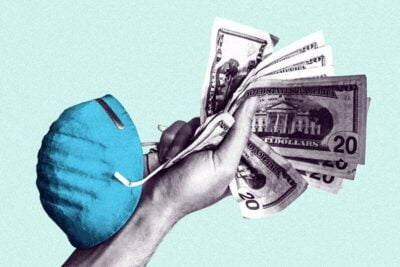 A hand clutching a stack of money and a surgical mask.