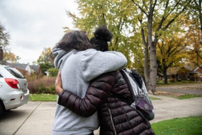 A girl and her mother embrace on a fall day.