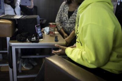 A girl wearing a neon yellow sweatshirt sits in front of a laptop in a cafe.