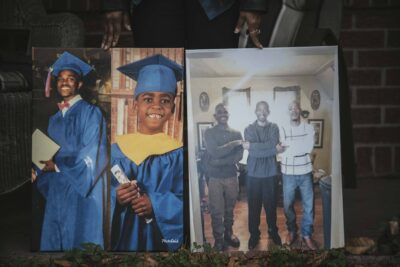 "Jeanette McClenton holds photographs of her son Duntate Young in a composite with his oldest son (left) and with his father, Leanell ""Troy"" McClenton, and his cousin (right) while standing for a portrait outside her home in West Memphis, Arkansas."