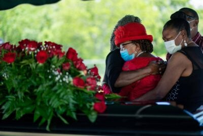 Two women embrace aside their brother's casket at his funeral service.