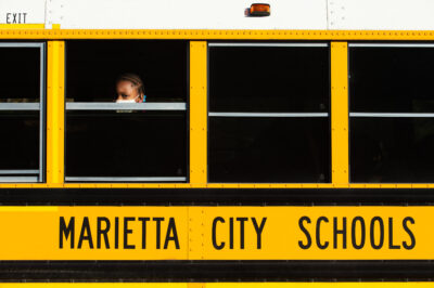 A student looks out of a school bus window.