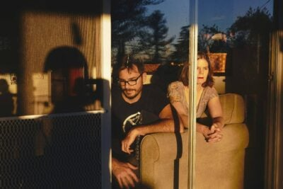 Peter Kalmus and Sharon Kunde sitting in magic hour light in their home.