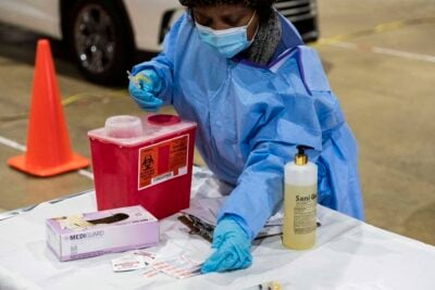 A nurse in blue PPE preparing vaccines.