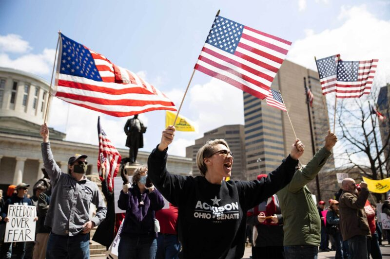 Demonstrators wave flags outside of the Statehouse in Columbus, Ohio, last month during a protest against the state's stay-at-home order. (Megan Jelinger/AFP via Getty Images)